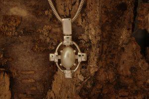 Fotografie eines Perlanhängers im Kreuzdesign